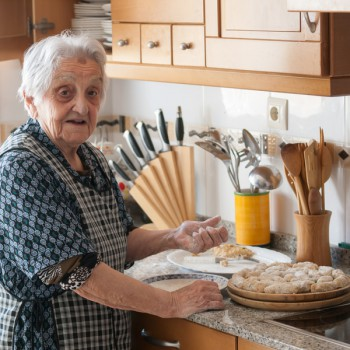 Elderly woman preparing croquettes at home